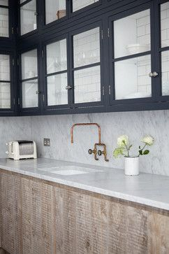 One wall of the kitchen features black cabinets, painted with Railings estate eggshell from Farrow & Ball. They are combined with metro tiles inside the glass-fronted cabinets, carrara marble worktops and splashbacks, and rustic-looking timber on the base units for the multi-textural effect