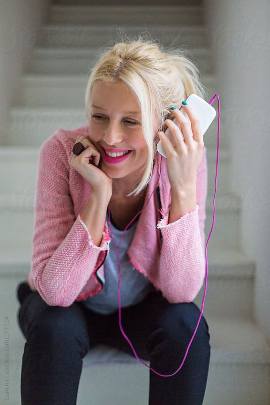 Smiling blonde woman listening to music on her mobile phone.