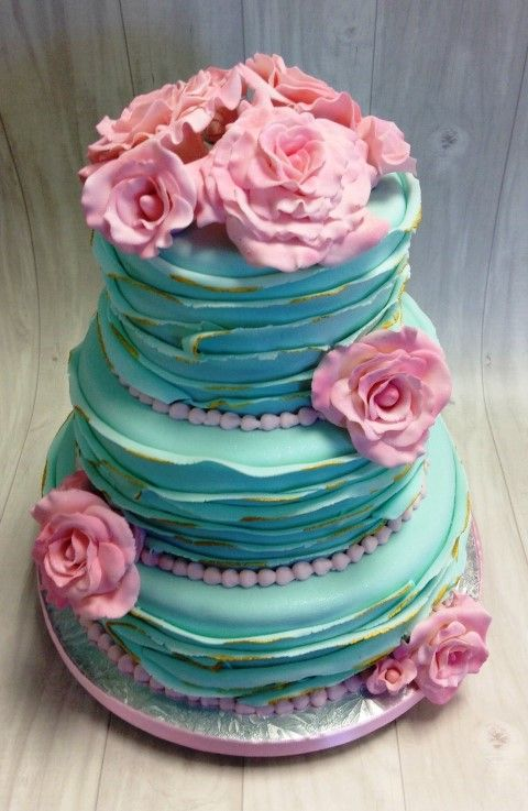 stunning aqua 3 tier wedding cake. Ruffled layers with golden brush edges. Pink beading and stunning pink hand made roses.