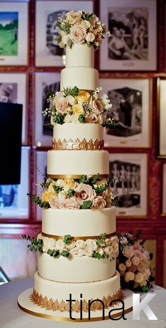 Beautiful antique gold borders on an ivory cake.  Tiers dressed with fresh flowers.