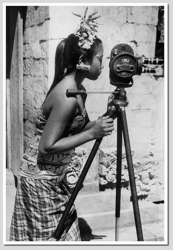 Balinese girl with a movie camera of a tourist, 1935, photographer unknown.