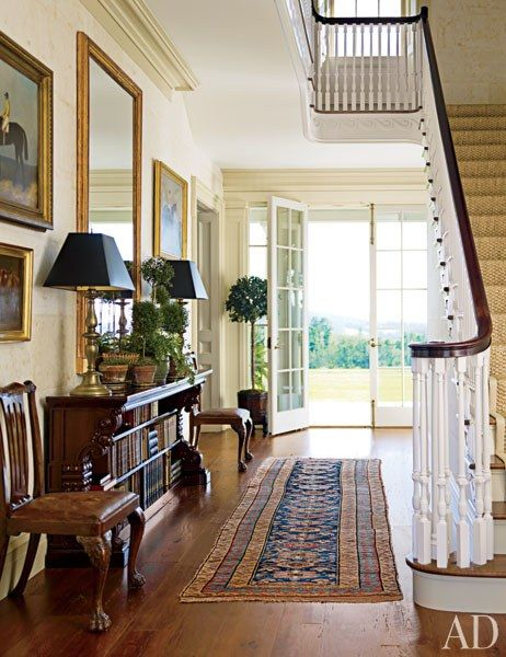 In the entrance hall, the antique English gilt-wood mirror and the 19th-century Irish mahogany bookcase are both from Niall Smith Antiques | archdigest.com