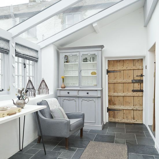 Soothing grey conservatory with white walls and slate flooring