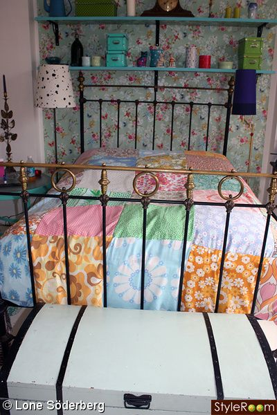 Our bedroom.  Old metal bed, some colorfull walpaper and shelves. Bedsheet is of my own making. Old vintage fabric, sewn together in squares.