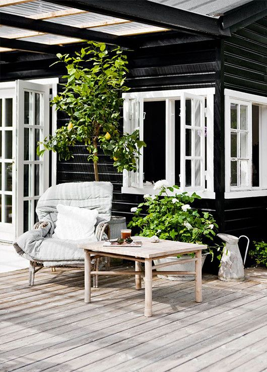 Black painted weatherboard house, white window frames and door frames, potted lemon tree, timber decking