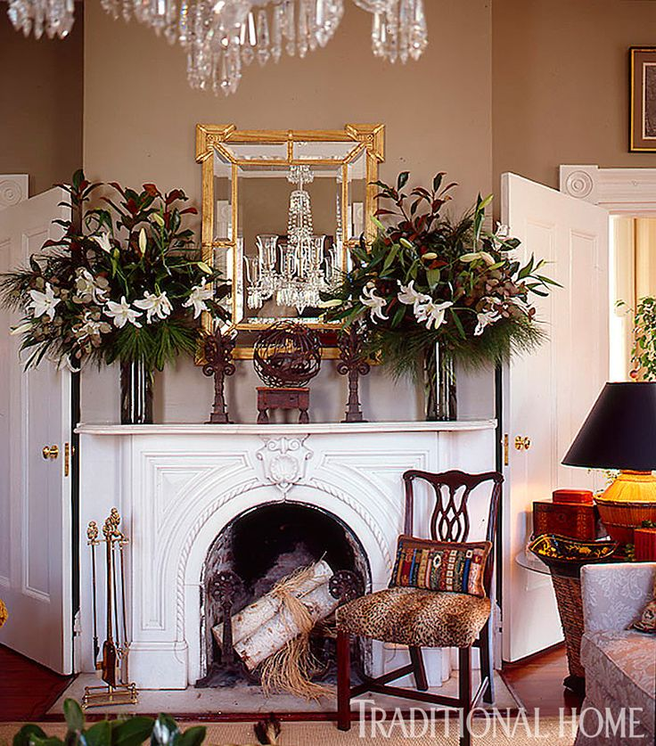 Vases containing white lily flowers and greenery add holiday flair to the formal mantel in lieu of a more traditional garland. - Traditional Home ® / Photo: Colleen Duffley / Design: Jo Edwards