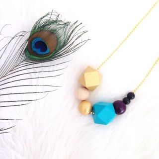This gorgeous necklace is exclusively made for Brindie! Beautifully handmade wooden geobead necklace featuring a regal combination of colours found in peacock feathers - gold, black, turquoise & purple.   The necklace is comprised of 7 geometric and spherical beads ranging in size from 8mm-30mm.    Each bead is painted in lovely silky acrylic and finished with several coats of non-toxic varnish to ensure it is safe to be worn next to perfume.   As the beads are hand painted, slight varia...