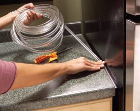 Keep crumbs from falling into the gap between your countertop and refrigerator by filling the void with clear plastic tubing. You can purchase it at home centers in several widths.