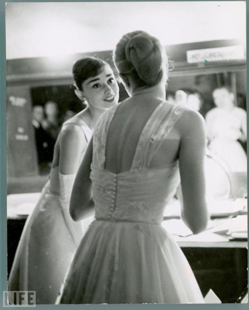 Audrey Hepburn and Grace Kelly chat backstage at the Academy Awards in 1956, where both appeared as presenters.