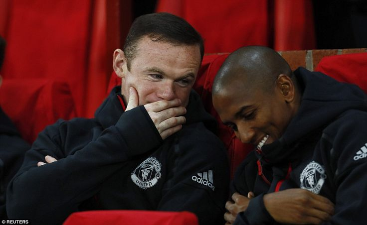 Rooney shares a joke with Ashley Young while sitting on the United bench before the game at Old Trafford