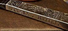 Clara Peeters: detail van Stilleven met kazen, amandelen en krakelingen. ca. 1615. Op het zilveren bruidsmes zette Peeters haar signatuur. Slow Food: stillevens uit de Gouden Eeuw, Mauritshuis.