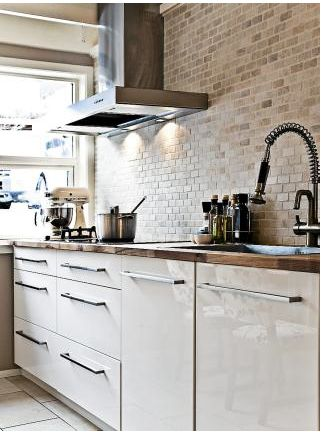 Love the marble mosaic backsplash - wall finish. Like the cream laquer kitchen base cupboards - would be smarter without handles. Iroko wood tops - warm - good combo with cream cupboards.