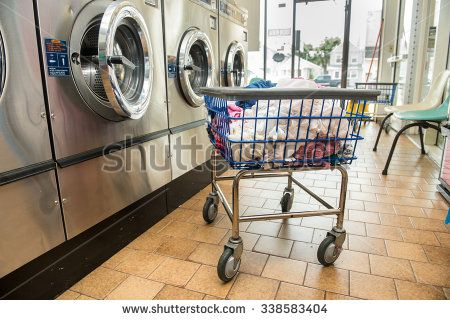 Industrial washing machines in a public laundromat, with laundry in a basket - stock photo