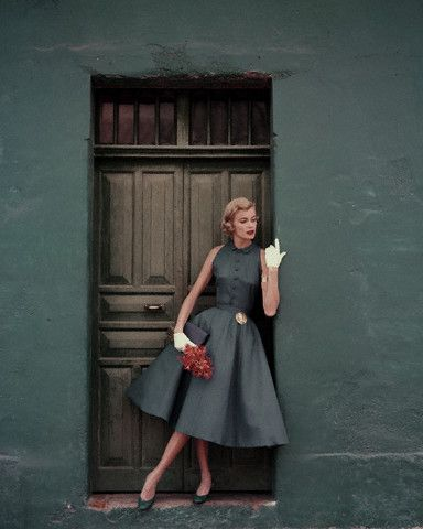 Model in two-piece slate blue dress by Heatherlane in McBratney Irish linen, Shantung clutch by MM, Pappagallo pumps, and golden medal pinned to the belt by Kendall-Smith. Circa May 1955.