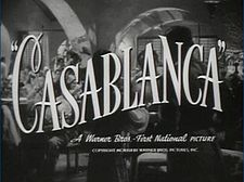 "Black-and-white film screenshot with the title of the film in fancy font. Below it is the text ""A Warner Bros. – First National Picture"". In the background is a crowded nightclub filled with many people."