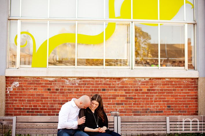 a photo of a couple kissing on the shoulder at an eng shoot at wychwood barns