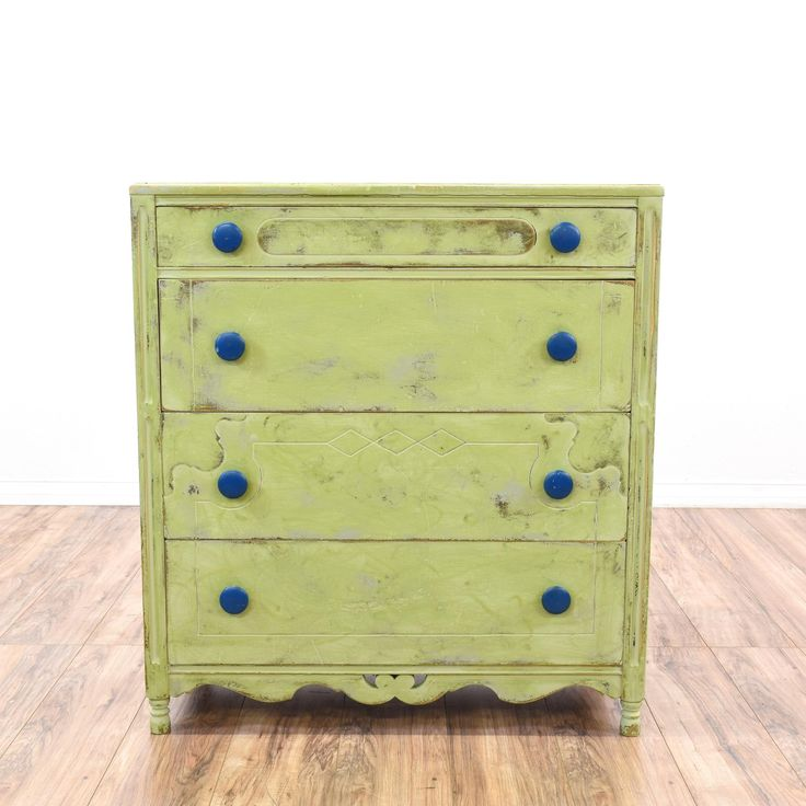 This shabby chic dresser is featured in a solid wood with a distressed light green paint finish. This chest of drawers is in good condition with 4 large drawers, carved trim and round blue handles. Perfect storage piece with tons of charm! #shabbychic #dressers #chestofdrawers #sandiegovintage #vintagefurniture