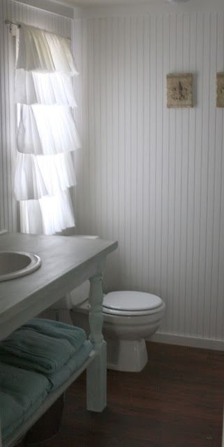 Ruffle curtains tend to dominate a space, but for this bathroom, the glow back-lit white fabric works well.