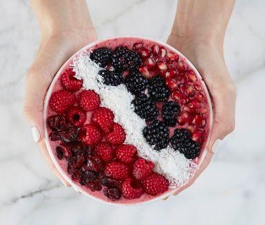 Den här syrligt fräscha frukost-bowlen är en utmärkt väckarklocka för den morgontrötte. Yoghurt, mandelmjölk och apelsinjuice utgör basen och mixas med frysta hallon, tranbär och isbitar. Toppa i vackert mönster med bär, granatäpple och kokosflingor. En fröjd för öga och gom!