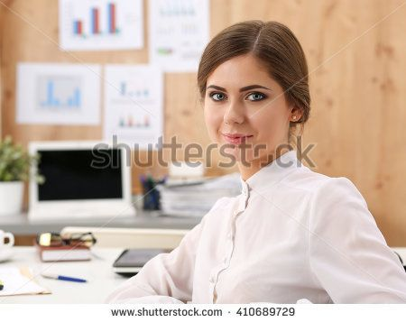 Beautiful smiling business woman sitting at office workplace half turn looking in camera portrait. Serious business and partnership, job offer, financial success, certified public accountant concept