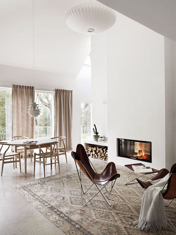 casa de campo, sillas butterfly chimenea muro de obra almacenaje troncos madera, silla Wegner Y chair