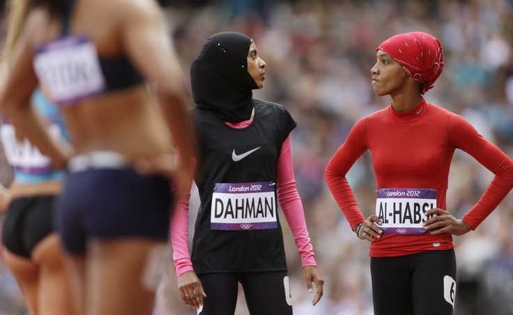 Yemens Fatima Sulaiman Dahman and Omans Shinoona Salah Al-Habsi, right, chat after a womens 100-meter heat during the athletics in the Olympic Stadium at the 2012 Summer Olympics, London, Friday, Aug. 3, 2012. (AP Photo/Anja Niedringhaus)