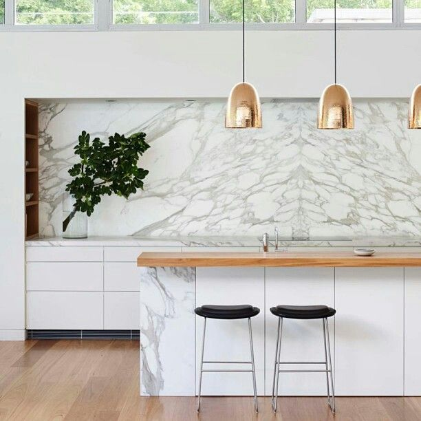 by Arent & Pyke, Sydney - bookmatched calacatta marble slab, gold pendants by Dunlin , open shelving in corner (left)