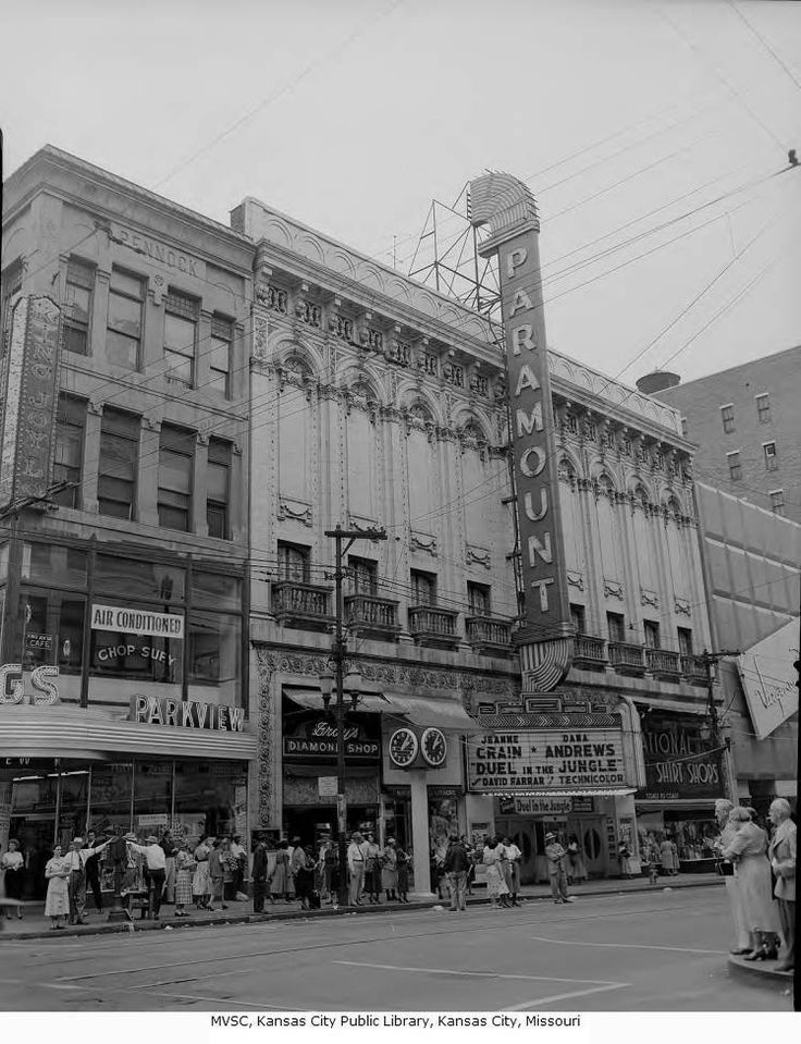 """Paramount Theater - Looking west across the intersection of 12th Street and Main toward the Paramount Theater, located at 1114 Main Street. The Paramount's marquee advertises """"Duel in the Jungle"""" with Jeanne Crain and Dana Andrews. Also located on Main are King Joy Lo Cafe, National Shirt Shop, and the Parkview Drugstore.    Date circa 1954    Notes This block was razed in the early 1970s and is occupied (2010) by City Center Square."""