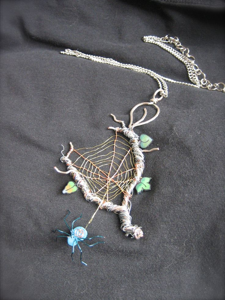 This is a spiderweb pendant I made from twisted wire of different finishes and gauges finished off with handmade spider and leaves.