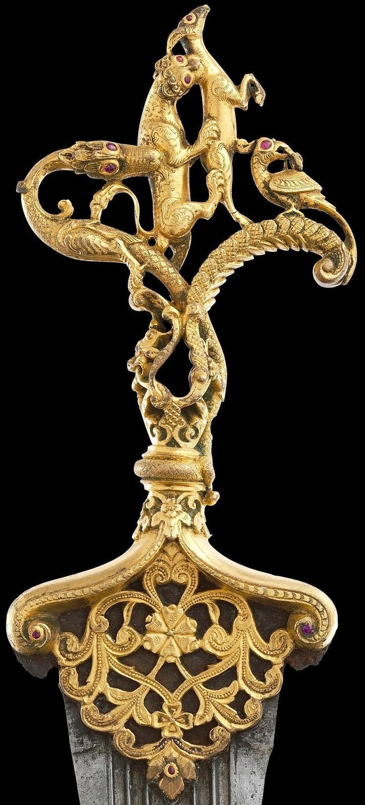 Indian (Deccan, Bijapur or Golconda) dagger, 16th c, cast copper hilt, chased, gilded, inlaid with rubies. Portraits of Sultan 'Ali 'Adil Shah of Bijapur 1558–80 show him wearing similar zoomorphic hilt daggers. In the ruby-studded hilt, a dragon whose tail wraps around the grip attacks a lion, which is attacking a deer, symbolic of the deity Garuda. Before the deer is a bird with a snake in its beak. Lower down is a mythical lionlike Yali, with floral scrolls issuing from its mouth. Met…