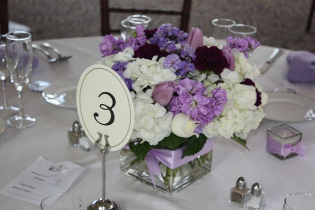 Lavender roses, purple carnations, blue iris, and purple stock were pulled through white hydrangea