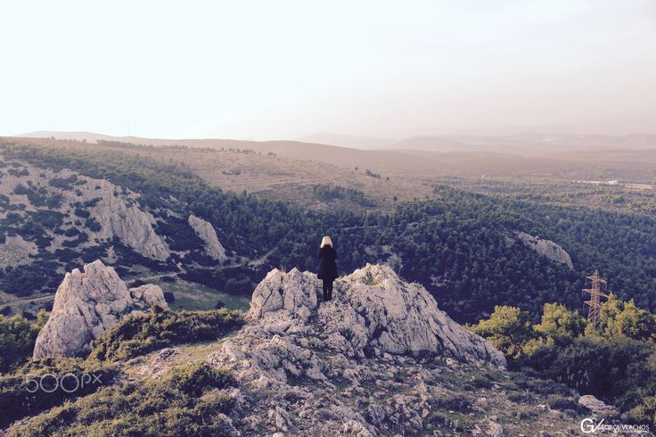 A woman watching the landscape on the edge of the cliff.