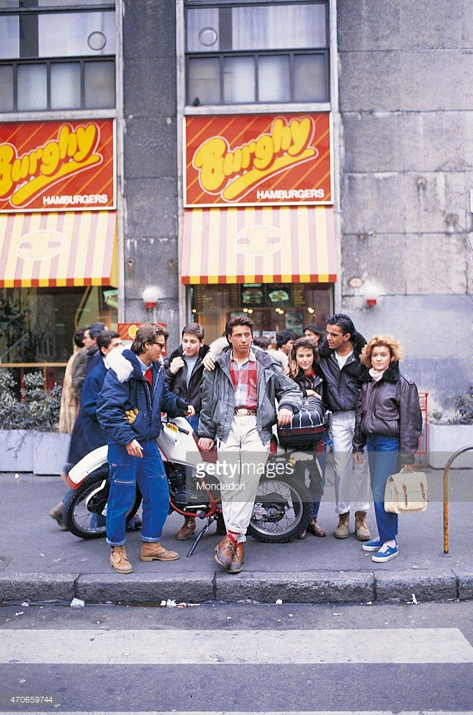 'The Burghy of Piazza San Babila, one of the restaurants of an Italian chain of American style fast food, is the traditional meeting place for boys and girls; it's the age of the so called ''paninari'', youngsters obsessively following the trend of wearing expensive designer clothes (1987, Milan, Italy). (Photo by Egizio Fabbrici\Mondadori Portfolio via Getty Images)' - Paninari
