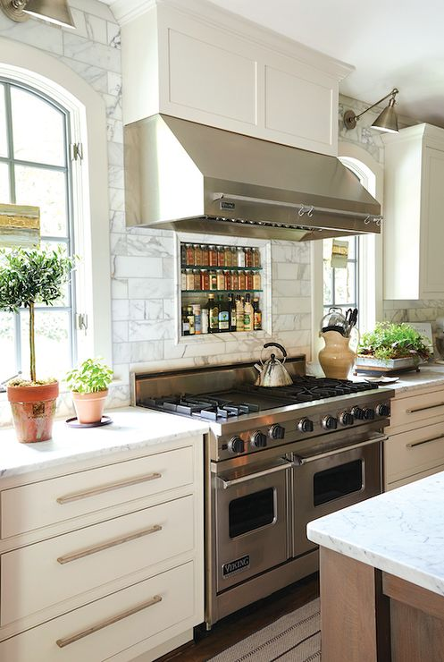 Beautiful kitchen features a stainless steel vent hood which stands over a marble tiled cooktop ...
