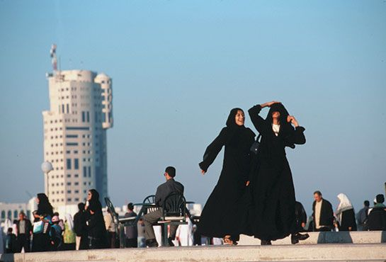 Two women dancing in the streets of Qatar wearing black abayas, long black full body cloaks that covers the hair and veils the face. This garment protects upper class women from male glades.