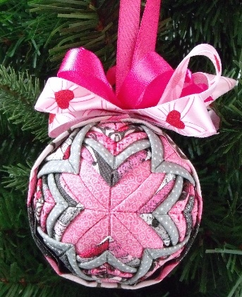 Alpine Shooting Star Quilted Ornament  This ornament measures 3 inch's it is done in the cathedral pattern. There are 5 different color fabrics each are all alternate between each other. Each piece of fabric is fold by hand. The top has a pink satin ribbon with hearts on it and a darker pink satin ribbon bow with attached hanger. Hang it in your car, give as a gift for valentines day or just sitting in a valentine bowl.