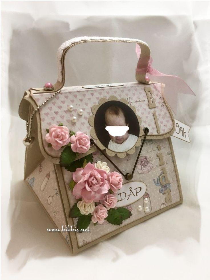 En dåpsveske til skjønne Elida. Laget i kraftkartong og Maja papirer. Pyntet med blomster, blader, halvperler, charms, bånd, blonde og en...