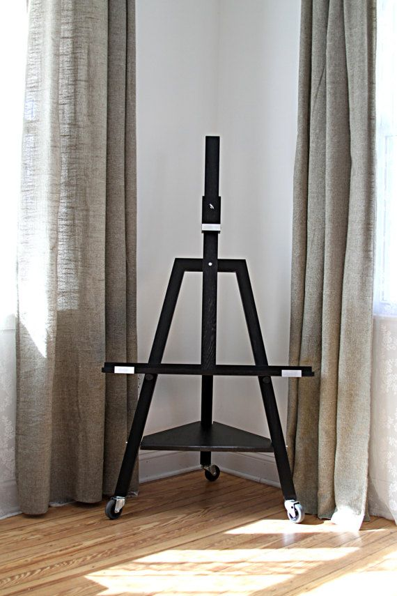 A beautiful minimalistic TV easel. Made out of Red Oak. Black Ebony finish. Also available in Golden Oak, Red Mahogany, Dark Walnut stains finished with a hard wax oil for durability and to keep the timber looking natural.  The easel is slightly tilted backwards about 10º for better stability and aesthetic look. Fits TV sets up to 55. Footprint: 30 width, 24 depth, 32 ledger width, 24 from the floor to the ledger, 10 from the floor to the utility shelf, 56 tall.  If you do not own a TV, you…