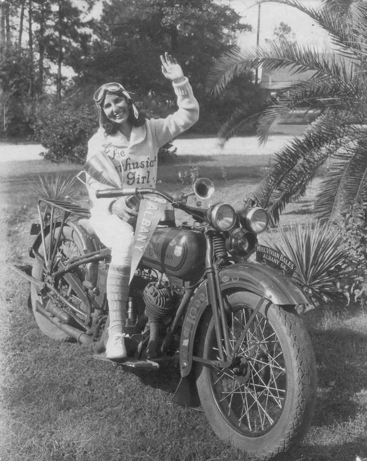 """Vivian Bales, """"Enthusiast Girl,"""" on her 1929 45 Twin D model Harley-Davidson.  On June 1, 1929, Ms. Bales embarked on a 5,000 mile, 78-day motorcycle tour.  She stopped at several Harley dealerships along the way, and even met President Hoover.  Although Harley-Davidson was not an official sponsor, they did provide Ms. Bales two nifty sweaters like the one she has on here."""