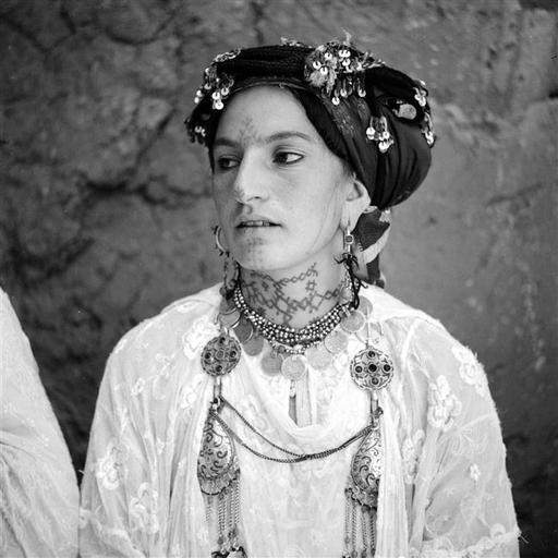 - Besancenot Jean (1902-1992) Femme zaïan en tenue traditionnelle typique. Son diadème est fait d'une masse de cordelières, khiout, enturbannant la coiffure. Aux fibules rehaussées d'émaux cloisonnés bleus et de cinq cabochons rouges, tissernas, sont accrochés des pendants en forme de poires, lanibrat. Les tatouages sur le visage et le cou sont caractéristiques de la tribu.- Arago