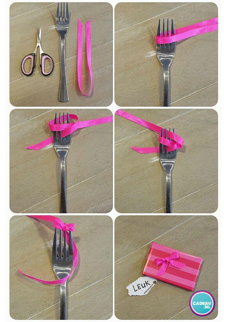 Cadeau inpaktip: Leg het lintje als een lus om de vork. Trek 1 uiteinde onderlangs door de tanden en trek het andere uiteinde bovenlangs door de tanden. Maak nu aan de achterzijde van de vork een knoopje van de twee uiteinden. Schuif het strikje van de vork en knip de lintjes op de gewesnte lengte. Voilá! Je hebt een perfect strikje voor op je cadeau. #cadeau #inpakken #geschenkverpakking