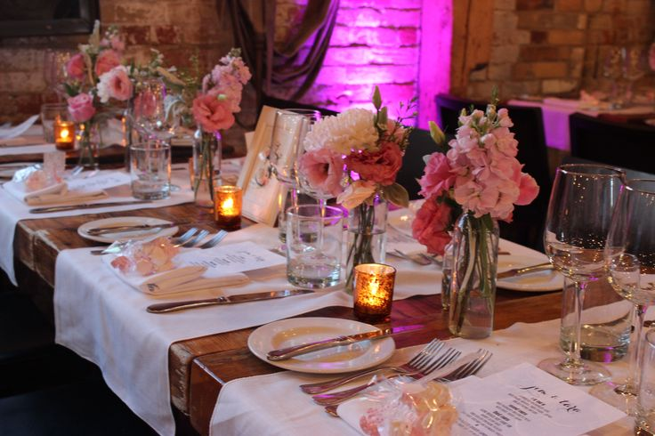 Bud vases of pink blooms along gallery tables