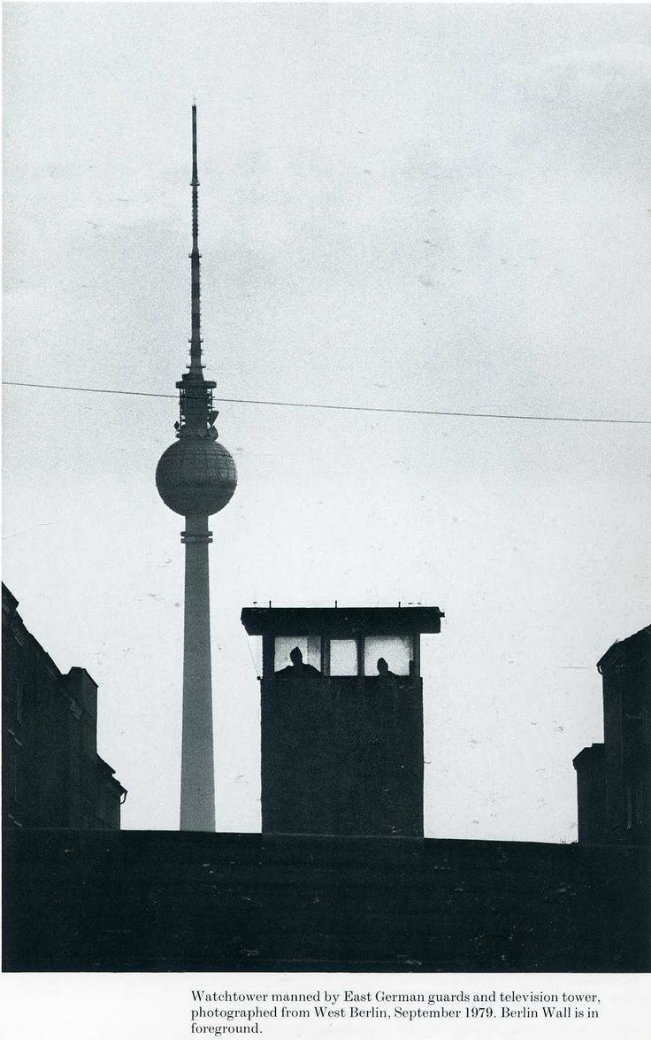 Alfred Eisenstaedt. Watchtower manned by East German guards and television tower, photographedfrom West Berlin, September 1979. Berlin Wall is in foreground.