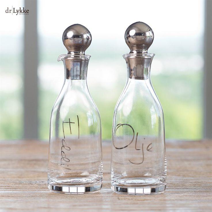 """Nydelige glassbeholdere for eddik og olje fra dr.Lykke. Beholderne har påskrevet """"Eddik"""" og """"Olje"""" har en nydelig utforming med smakfulle detaljer som garantert vil falle i smak. Stor og blankpolert lokk for å avslutte de eksklusive glassbeholderne.  Kan også brukes som nydelige karafler!"""
