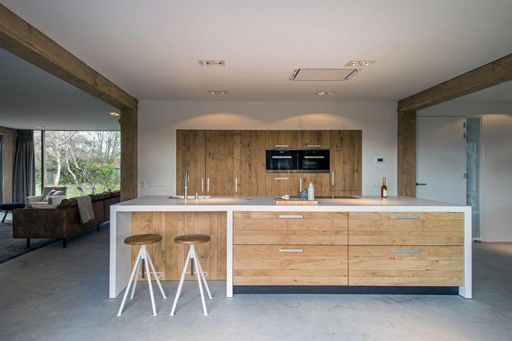 Woonkeuken in landelijk interieur met groot kookeiland en hoge wand met inbouwapparatuur van ruw eiken - maatwerk van JP Walker