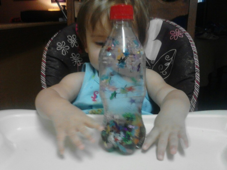 Sensory Bottle ... Confetti, dice, beads, water & a bottle. My 14 month old has been playing with this for HOURS!