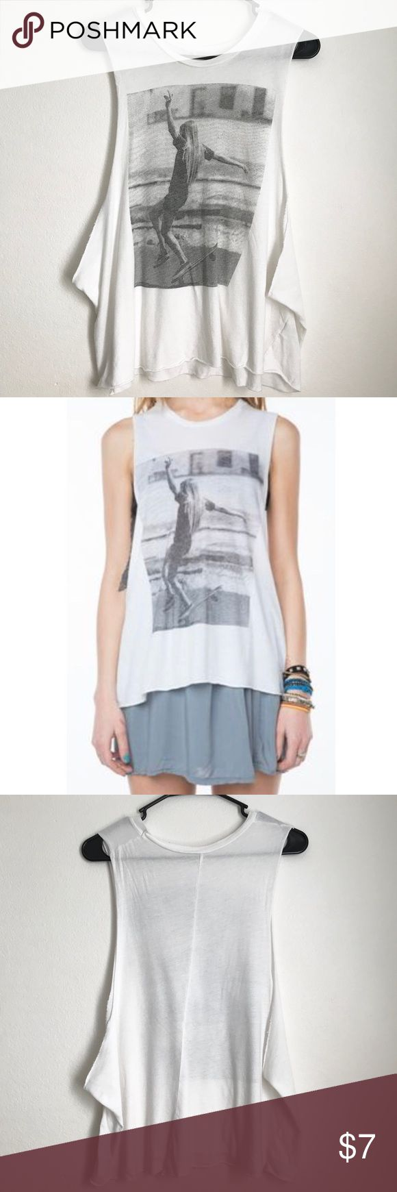Brandy Melville White Muscle Tank Brandy Melville white muscle tank with a skater girl graphic on the front and low cut arm holes.    Super cute for over swimsuits or sports bras - or going out paired with denim! Brandy Melville Tops Tank Tops