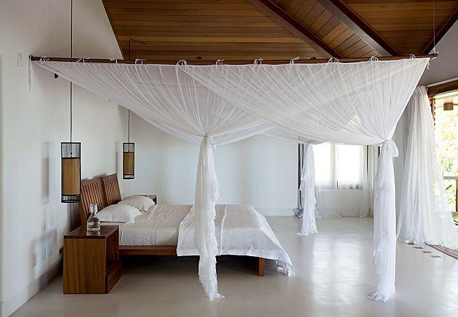 A suíte desta casa em Trancoso, litoral sul da Bahia, ocupa todo o pavimento superior, na ala íntima. Em torno da cama e dos criados, tecido mosquiteiro na cor branca, mesma cor da cortina e dos lençóis. O projeto é do arquiteto David Bastos