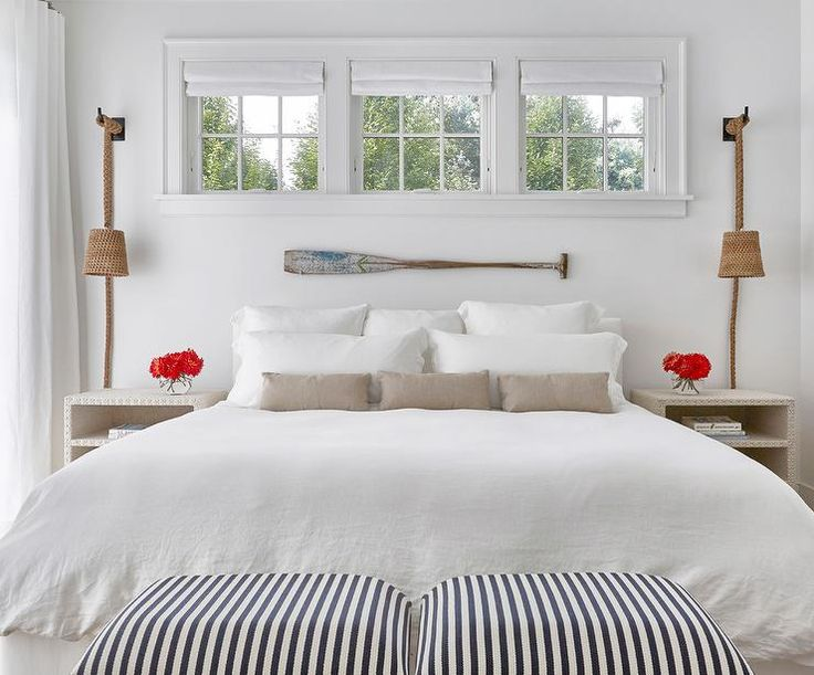 Cottage bedroom features three windows dressed in white roman shades placed over a decorative oar lining a wall above a bed dressed in white bedding and taupe pillows flanked by white linen nailhead open nightstands illuminated by rope wall sconces.