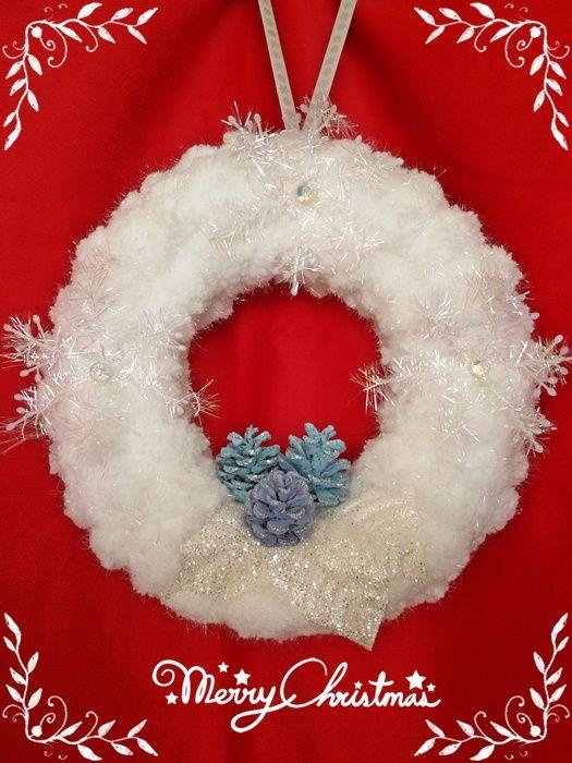 ghirlanda di Natale in polistirolo rivestita con lana, decorata con pigne dipinte, porporina e fiocchi di neve in plastica.